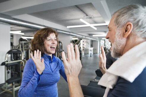 Happy senior man and woman high fiving after working out in gym - HAPF01664