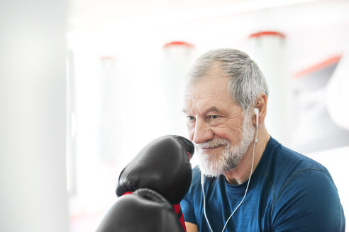 Fit senior man with earphones and boxing gloves in gym - HAPF01670