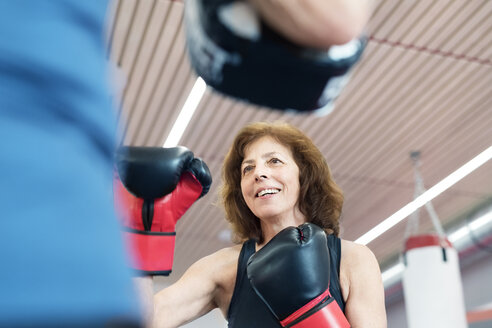Fit senior woman boxing with her coach - HAPF01682