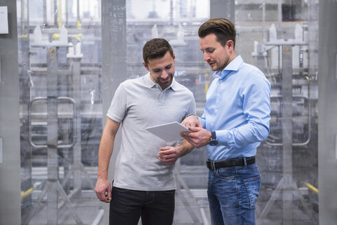 Two men with tablet talking in factory shop floor - DIGF02337