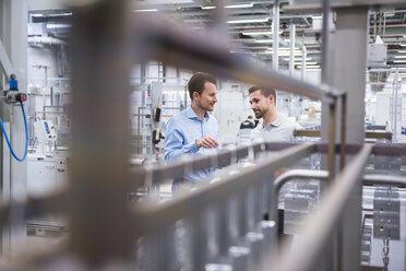 Two men talking in factory shop floor - DIGF02343
