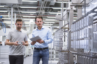 Two men with tablet talking about a product in factory shop floor - DIGF02349