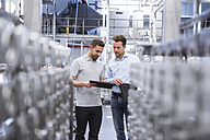 Two men with tablet talking in factory shop floor - DIGF02352