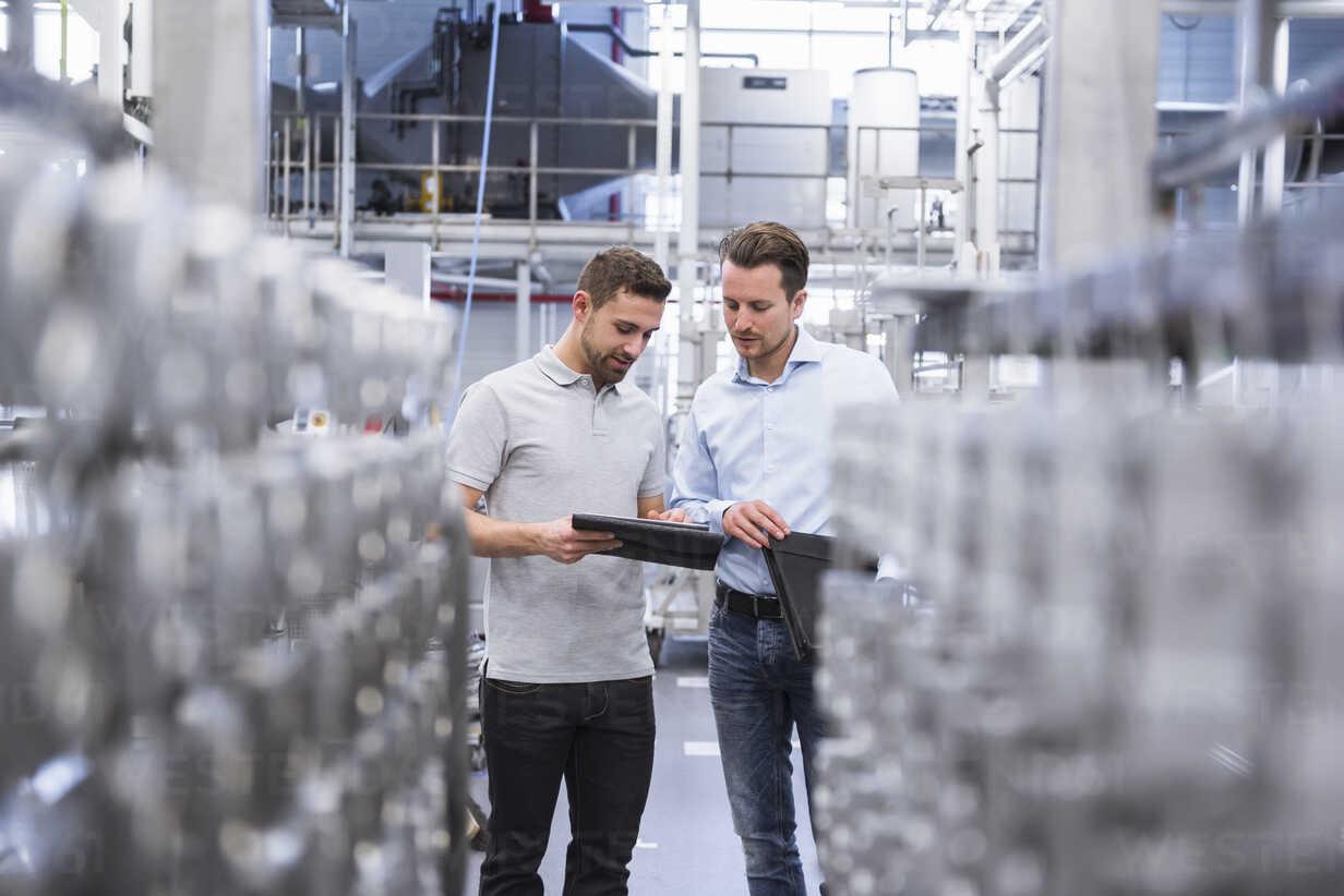 Two men with tablet talking in factory shop floor - DIGF02352 - Daniel Ingold/Westend61