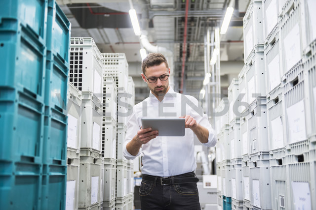 Man using tablet at boxes in factory shop floor - DIGF02373 - Daniel Ingold/Westend61