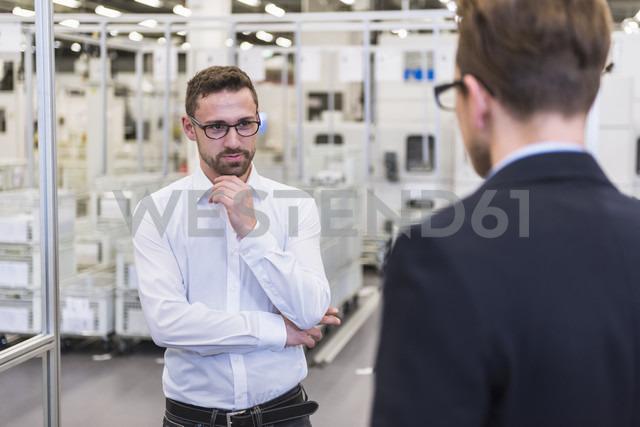Two men talking in factory shop floor - DIGF02376 - Daniel Ingold/Westend61
