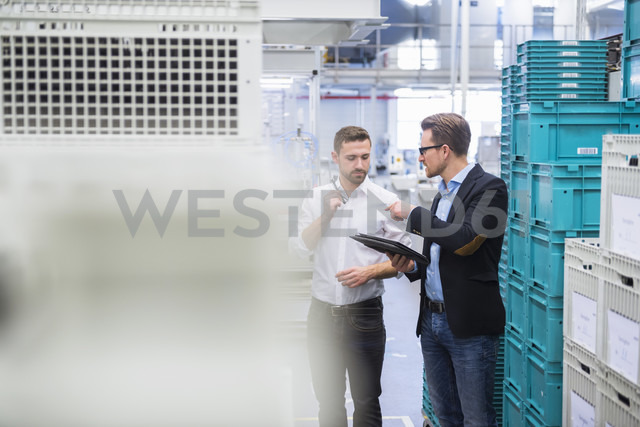 Two men with tablet talking at boxes in factory shop floor - DIGF02379 - Daniel Ingold/Westend61