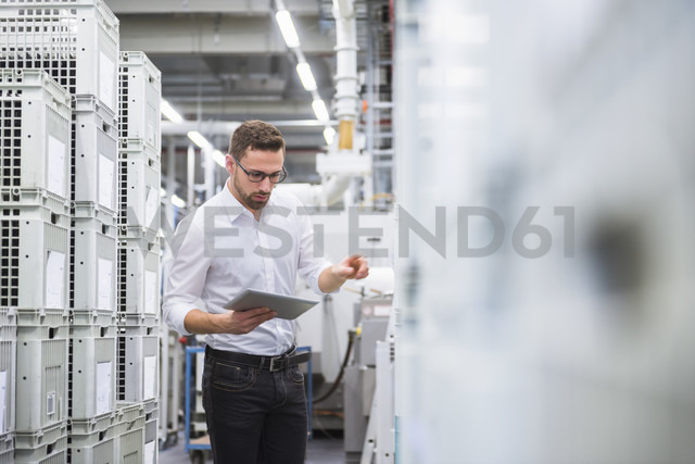 Man using tablet at boxes in factory shop floor - DIGF02382 - Daniel Ingold/Westend61