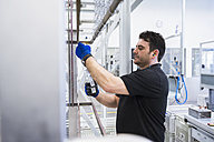 Man working in factory shop floor hanging products on rack - DIGF02394