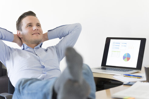 Relaxed businessman at desk leaning back - FMOF00249