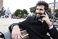 Portrait of smiling young man with full beard on the phone sitting on a bench - ABZF01982