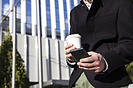 Man with smartphone and coffee to go, partial view - ABZF01991
