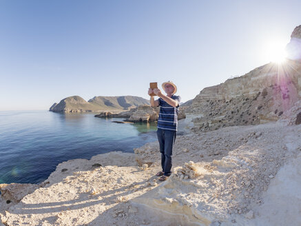 Spain, Andalusia, Cabo de Gata, man taking a selfie at the sea - LAF01834