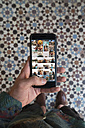 Morocco, man's hand holding smartphone with vacation snaps - KKAF00750