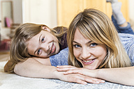 Portrait of smiling blond woman lying on the floor with her daughther - TCF05396