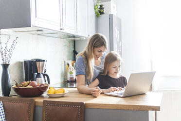 Mother and daughter using laptop in kitchen - TCF05399
