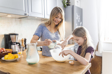 Mother and daughter preparing pancakes in kitchen - TCF05402