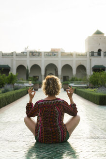 Morocco, Marrakesh, tourist sitting on the floor in a courtyard doing yoga - KKAF00789