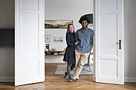 Smiling couple at home standing in door frame - SBOF00380