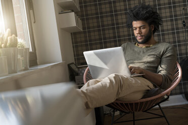 Man sitting in living room in armchair working on laptop - SBOF00383