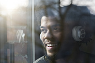 Man at window looking outside listening to music with headphones - SBOF00392