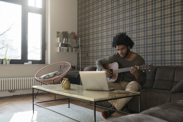 Man sitting in living room on sofa playing guitar in front of laptop - SBOF00401