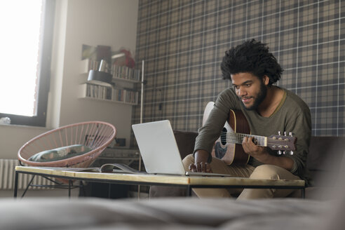 Man sitting in living room on sofa playing guitar in front of laptop - SBOF00404