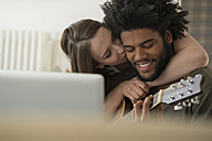 Close-up of woman kissing smiling man playing guitar in front of laptop - SBOF00407