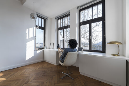Man sitting in minimalist empty room on chair - SBOF00428