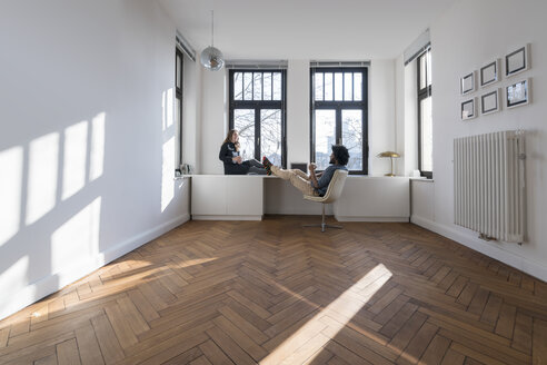 Smiling couple sitting in minimalist empty room talking - SBOF00431