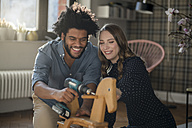 Smiling couple mounting rocking horse with cordless drill - SBOF00437