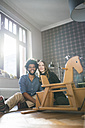 Smiling couple looking at camera in front of rocking horse - SBOF00440