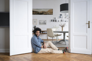 Man at home sitting on floor leaning on door frame in living room - SBOF00443