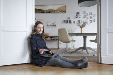 Smiling woman at home sitting on floor with laptop in door frame holding credit card - SBOF00446