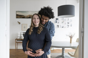 Smiling pregnant couple in living room - SBOF00455