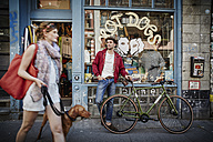 Germany, Hamburg, St. Pauli, Man with bicycle waiting in front of vintage shop, woman with dog coming out - RORF00823