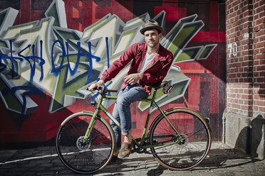 Germany, Hamburg, St. Pauli, Man sitting on bicycle in front of graffiti - RORF00832
