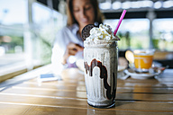 Glass of chocolate milkshake with cream on table - KIJF01447