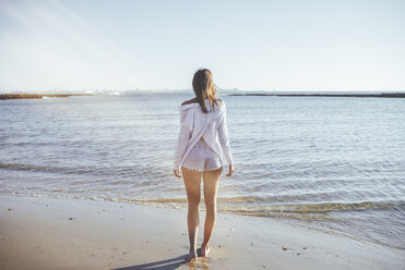 Back view of woman on the beach looking at the sea - KIJF01456