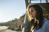 Young woman relaxing on the beach at sunset - KIJF01465