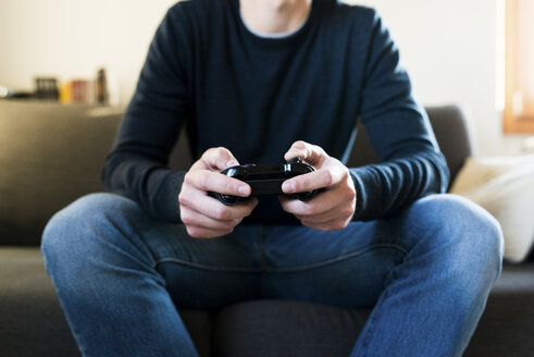 Man sitting on the couch playing with games console, partial view - FMOF00262