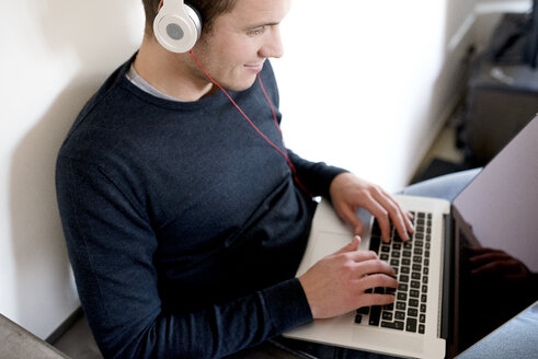 Man using laptop and headphones at home - FMOF00268