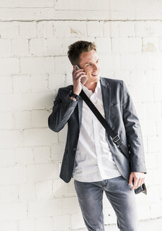 Young businessman using smartphone, standing in front of wall - UUF10590