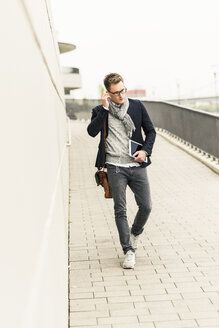 Young businessman walking in the street, carrying digital tablet and ear phones - UUF10605