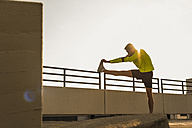 Young man stretching on parking level - UUF10614