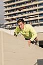 Young athlete exercising push ups on parking level - UUF10617