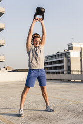 Young man exercising with kettle bell on a rooftop - UUF10623