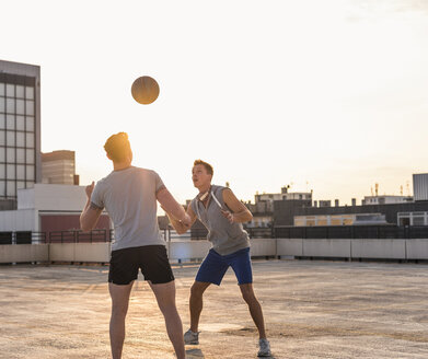 Friends playing basketball at sunset on a rooftop - UUF10638