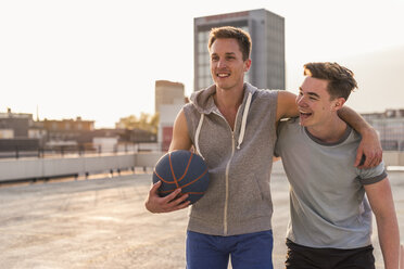 Friends playing basketball at sunset on a rooftop - UUF10641