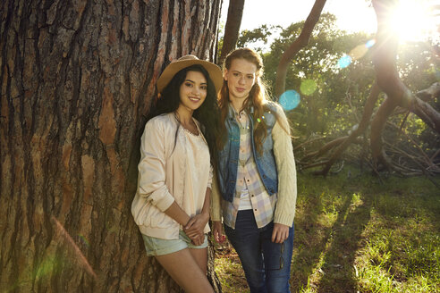 Portrait of two young women leaning against tree trunk - SRYF00428